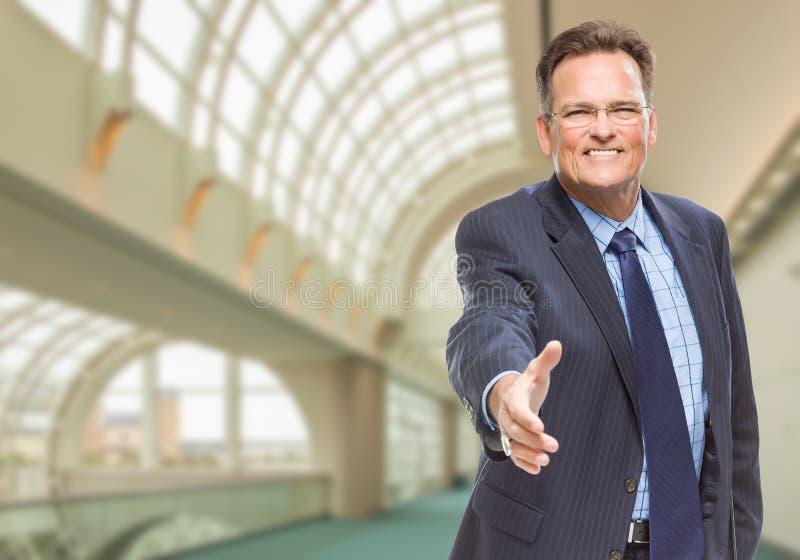 Homme d'affaires Reaching pour le bâtiment d'entreprise d'intérieur de secousse de main image stock