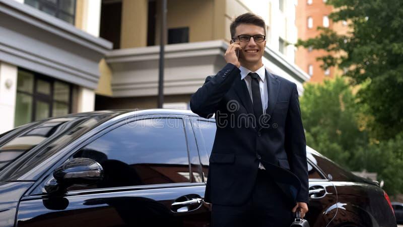 Homme d'affaires recevant de bonnes nouvelles, parlant au téléphone près de la voiture de luxe, succès image libre de droits