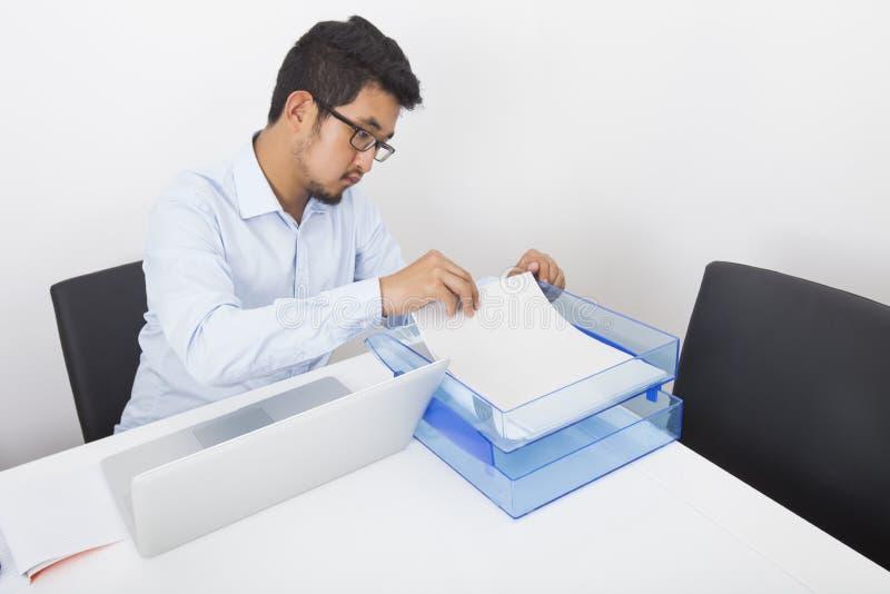 Homme d'affaires recherchant des documents au bureau dans le bureau photographie stock