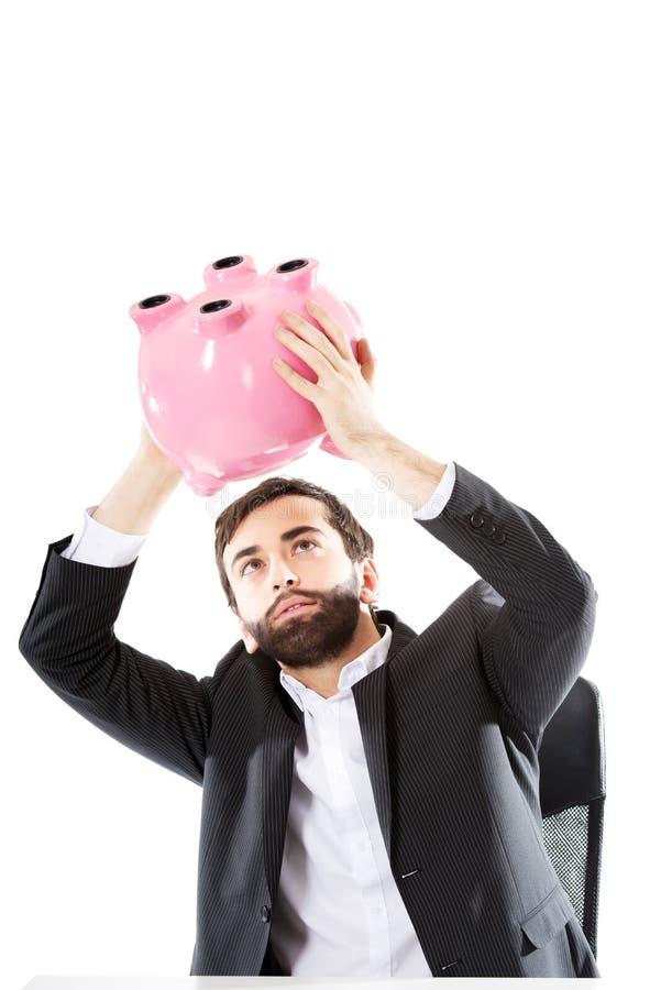 Homme d'affaires recherchant l'argent dans la tirelire photos libres de droits