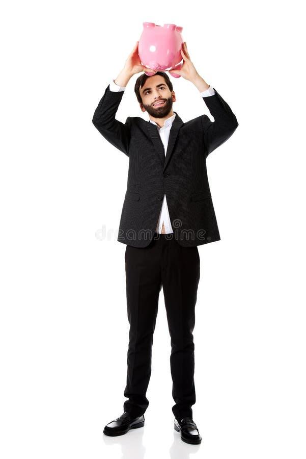Homme d'affaires recherchant l'argent dans la tirelire images stock