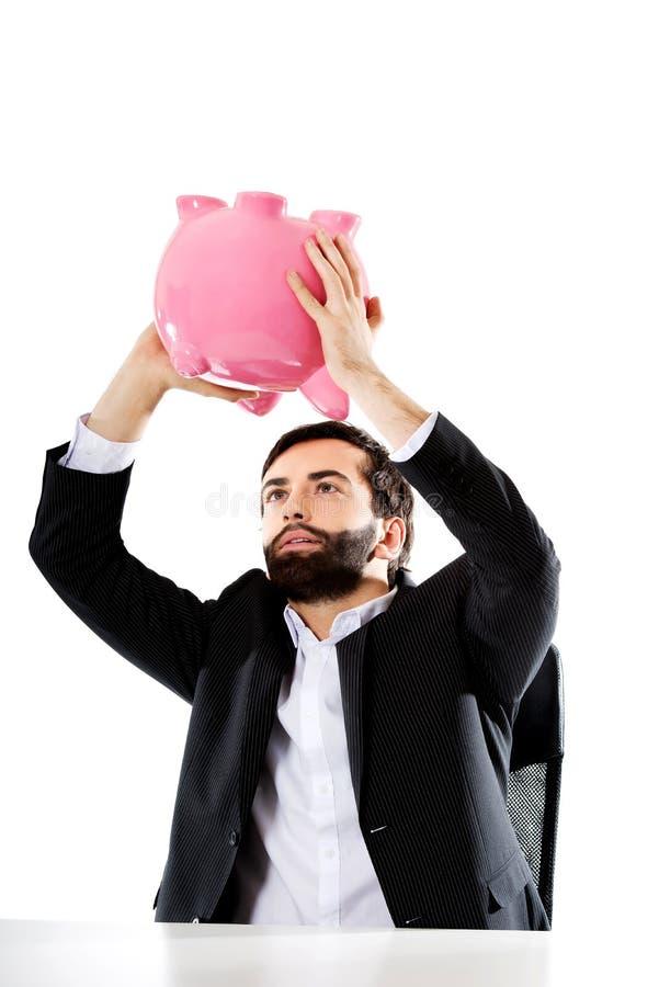 Homme d'affaires recherchant l'argent dans la tirelire photo stock