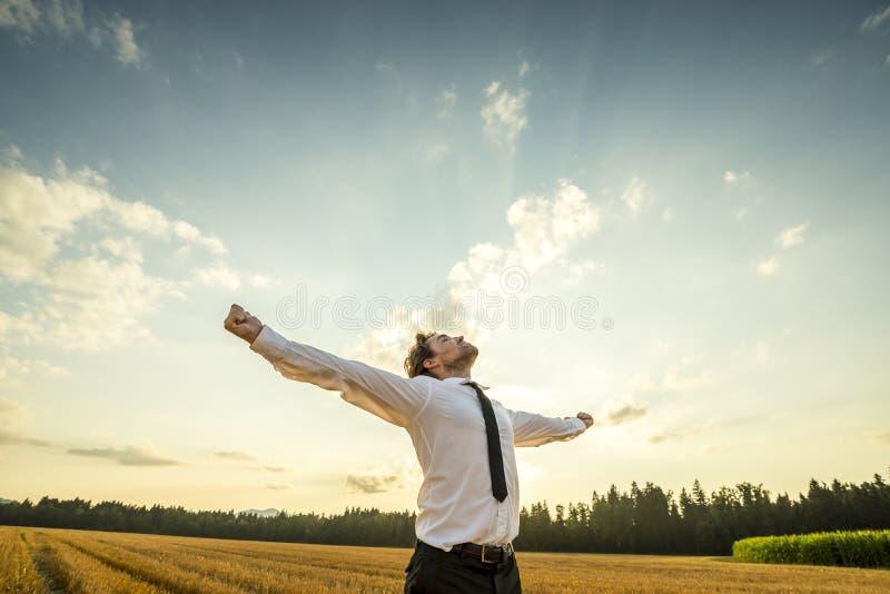 Homme d'affaires reconnaissant avec les bras ouverts au champ image stock