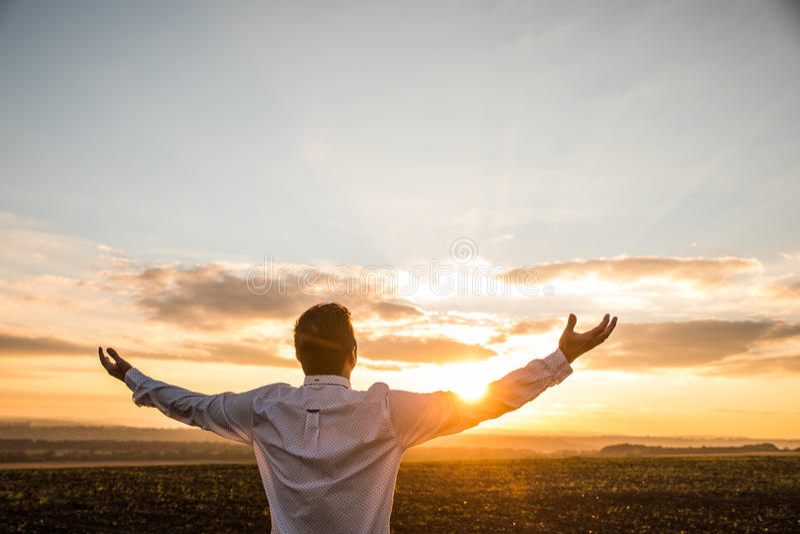 Homme d'affaires reconnaissant avec les bras ouverts au champ sur le coucher du soleil image libre de droits