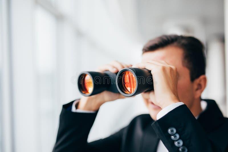 Homme d'affaires regardant avec des jumelles au-dessus des fenêtres panoramiques photo stock