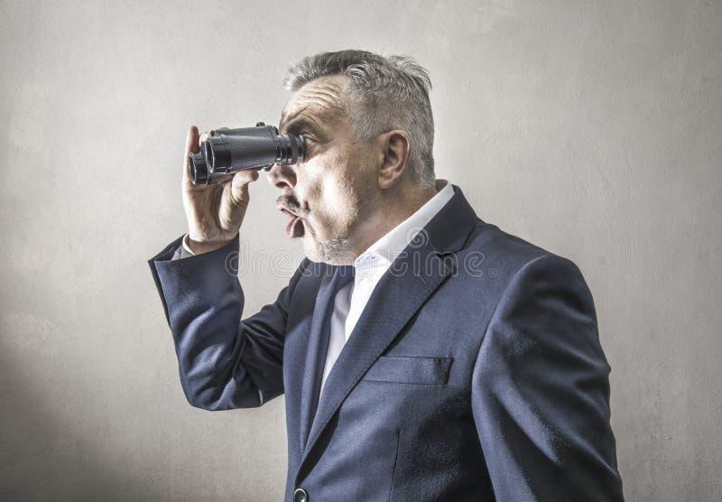 Homme d'affaires regardant avec des jumelles photos stock