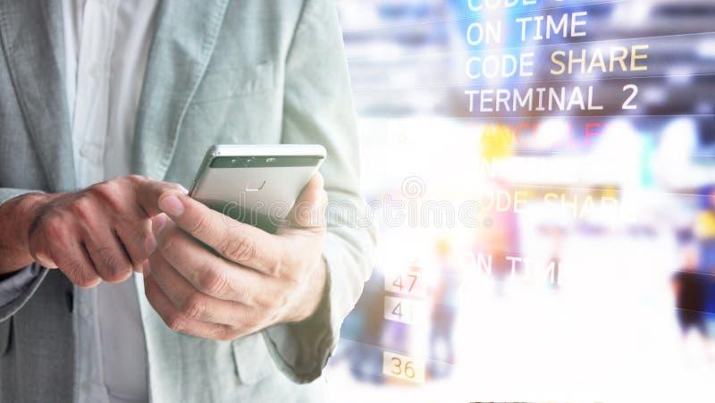 Homme d'affaires regardant des programmes de vol sur le mobile pour vérifier t image stock