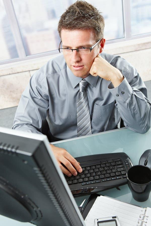 Homme d'affaires regardant l'écran dans le bureau photos stock