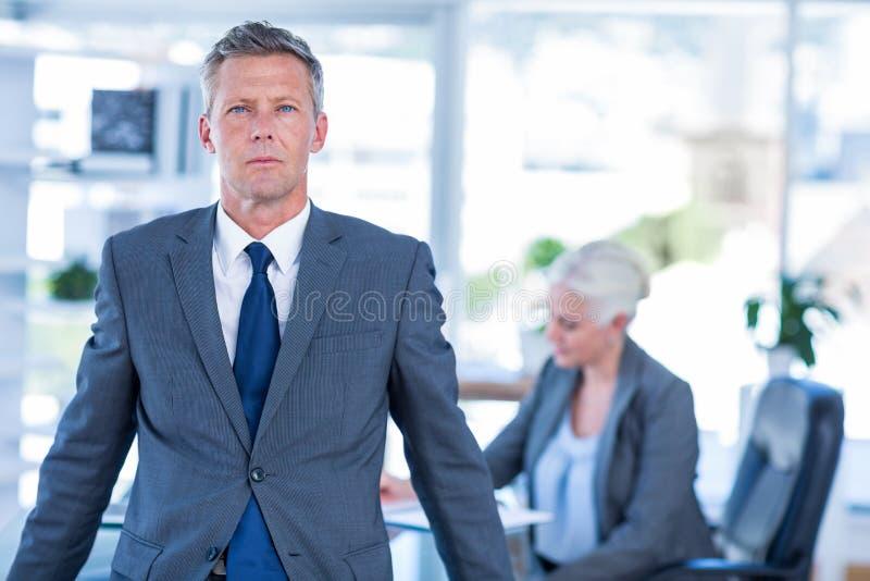 Download Homme D'affaires Regardant L'appareil-photo Avec Ses Collègues Derrière Lui Image stock - Image du affaires, bureau: 56481647