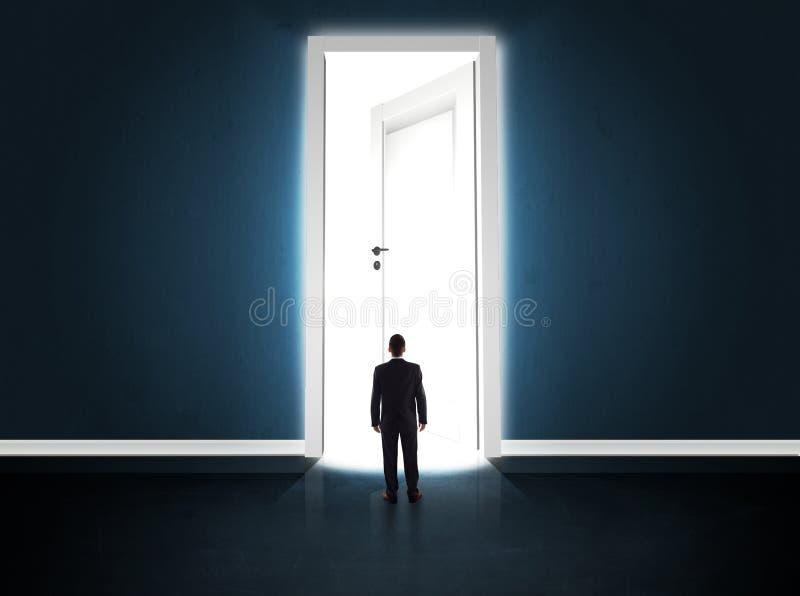 Homme d'affaires regardant la grande porte ouverte lumineuse photographie stock
