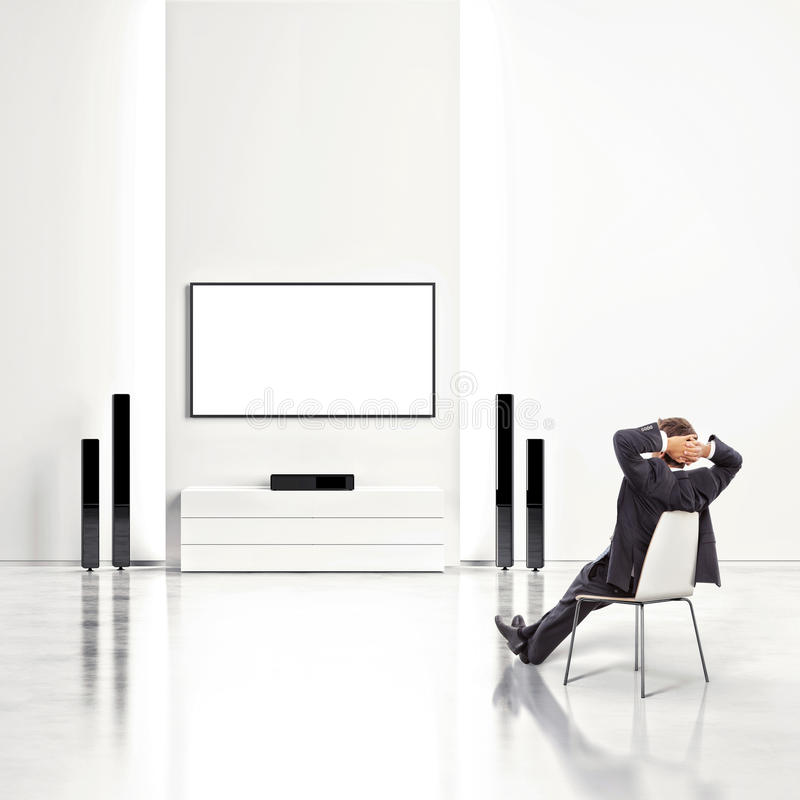 Homme d'affaires regardant la TV photographie stock