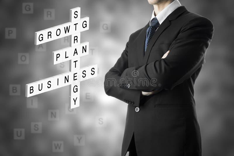 Homme d'affaires regardant le concept d'affaires par des mots croisé photo stock