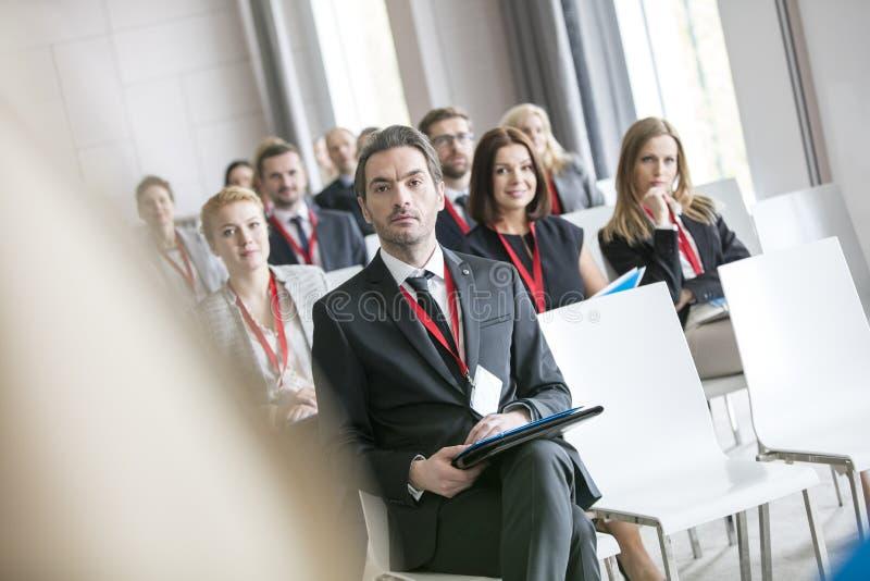 Homme d'affaires regardant le conférencier pendant le séminaire au centre de congrès photos stock