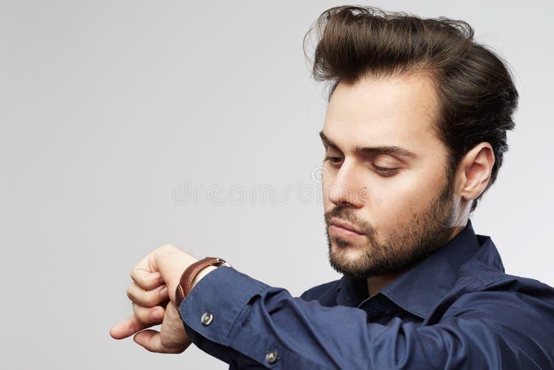 Homme d'affaires regardant le sien montre D'isolement sur un fond gris image libre de droits
