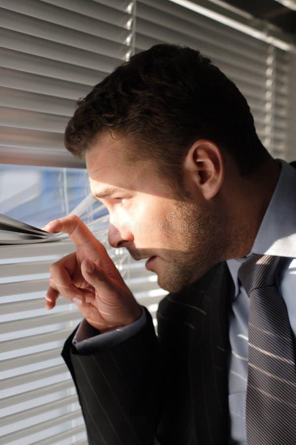 Homme d'affaires regardant par des abat-jour d'hublot photos libres de droits
