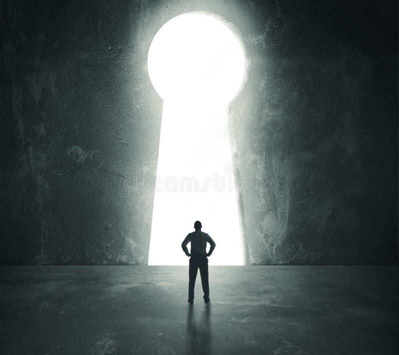 Homme d'affaires regardant par le trou principal image libre de droits