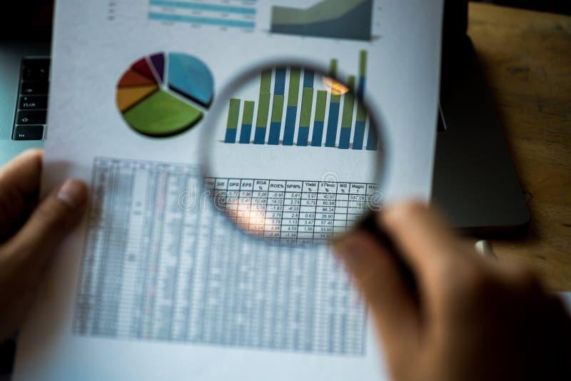 Homme d'affaires regardant par une loupe aux documents ?valuation et audit d'affaires Loupe sur un rapport financier images libres de droits