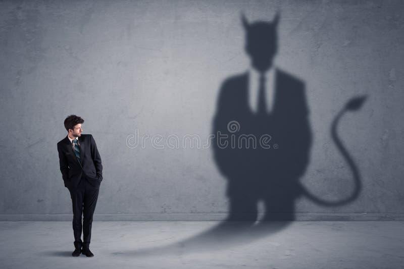 Homme d'affaires regardant son propre concept d'ombre de démon de diable images stock