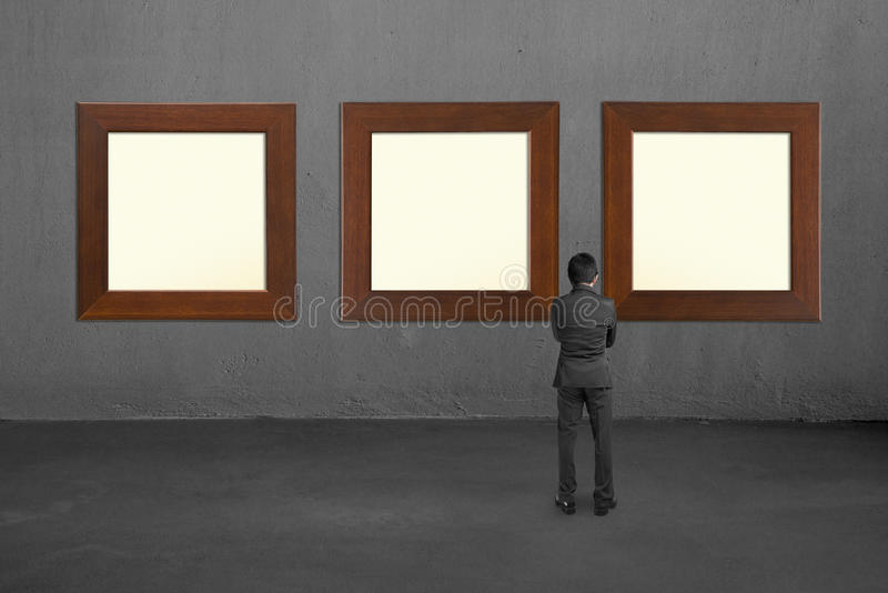 Homme d'affaires regardant trois cadres en bois en blanc sur wal concret photos libres de droits
