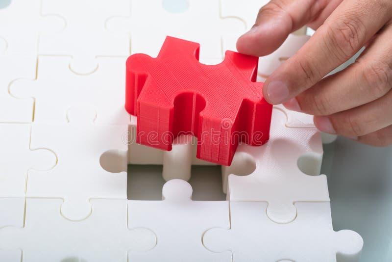 Homme d'affaires reliant le morceau rouge dans les puzzles denteux blancs photo libre de droits