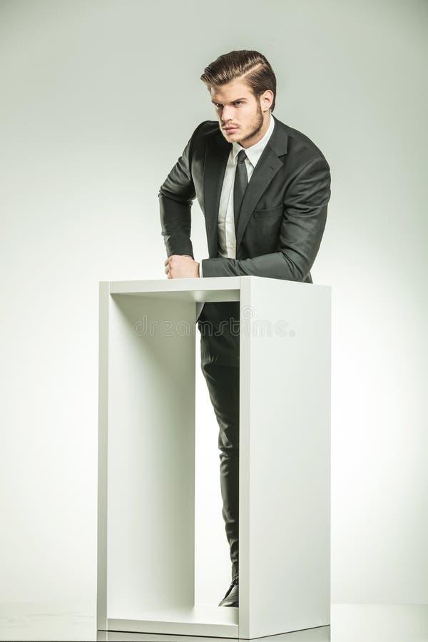 Homme d'affaires reposant son bras sur une table moderne blanche photographie stock libre de droits