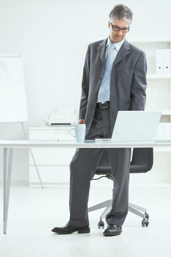 Homme d'affaires restant au bureau photographie stock