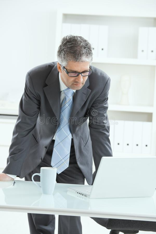 Homme d'affaires restant au bureau images stock