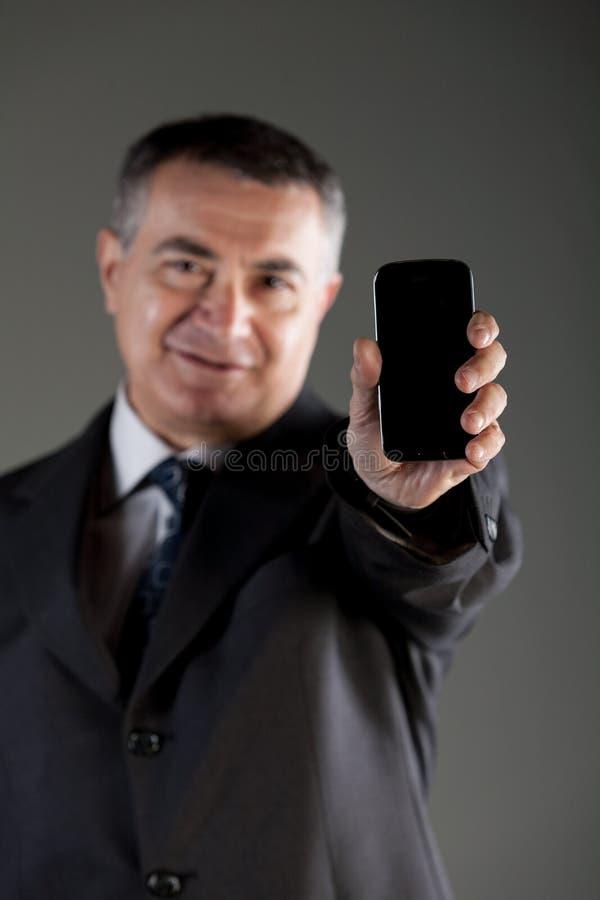 Homme d'affaires retardant un téléphone portable vide photo stock