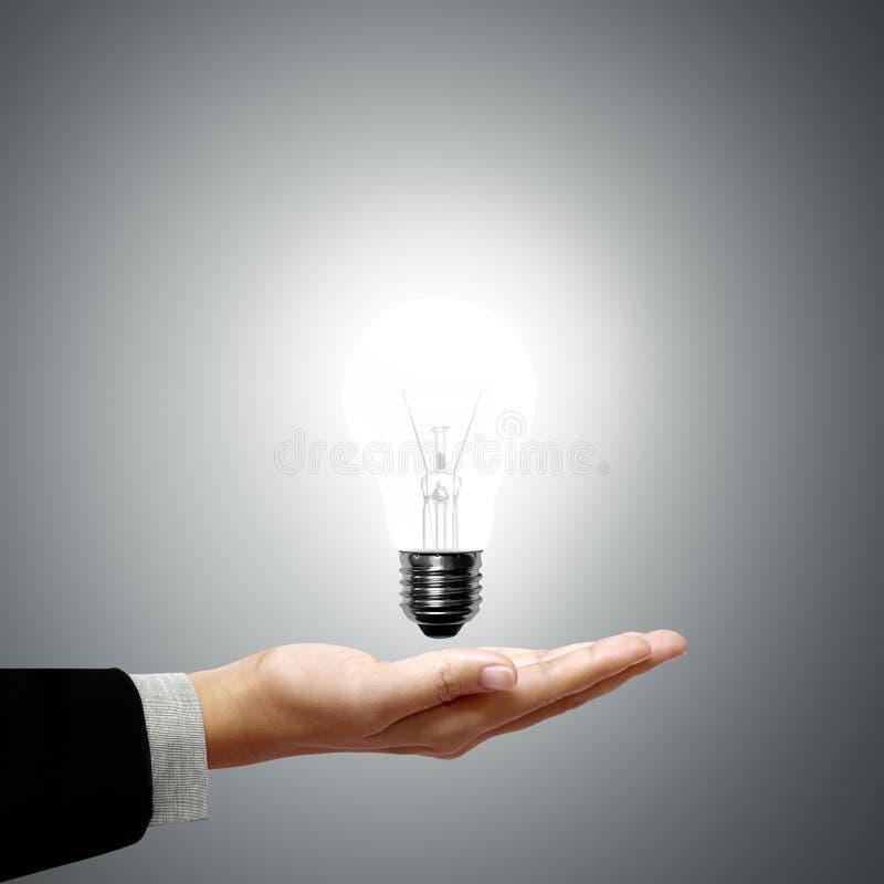 Homme d'affaires retenant l'ampoule dans sa main images stock