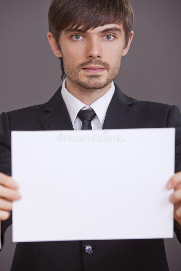 Homme d'affaires retenant le panneau blanc image stock