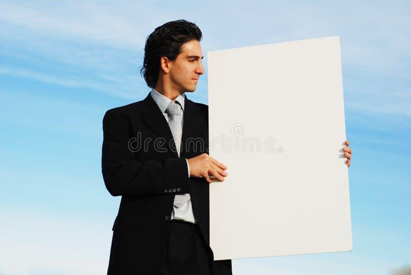 Homme d'affaires retenant le panneau blanc photos stock