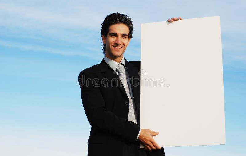 Homme d'affaires retenant le panneau blanc images stock