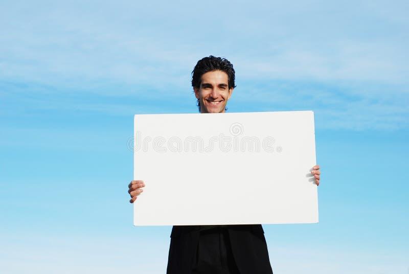 Homme d'affaires retenant le panneau blanc photo stock