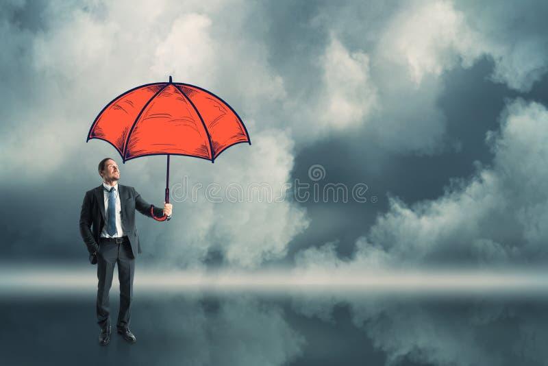 Homme d'affaires retenant le parapluie rouge photographie stock