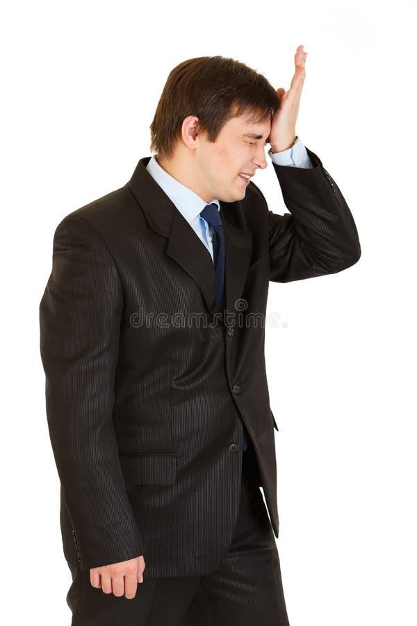Homme d'affaires retenant le sien main près du front image stock
