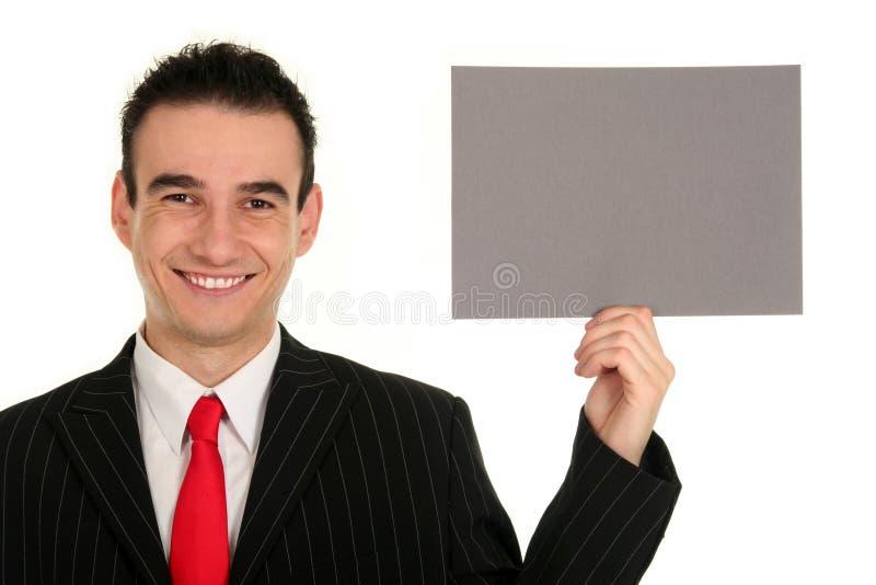 Homme d'affaires retenant le signe blanc photo stock