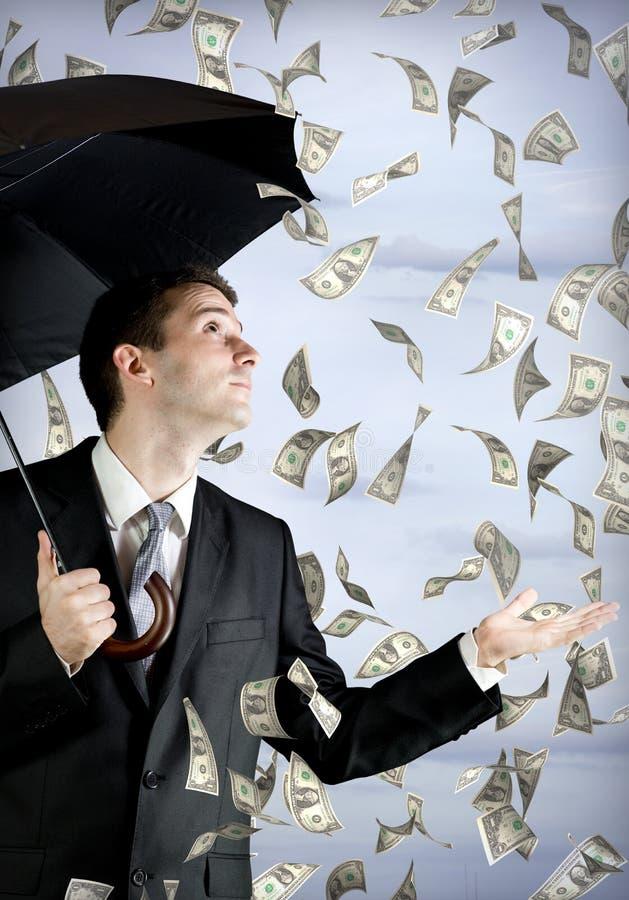 Homme d'affaires retenant un parapluie, chute d'argent photographie stock