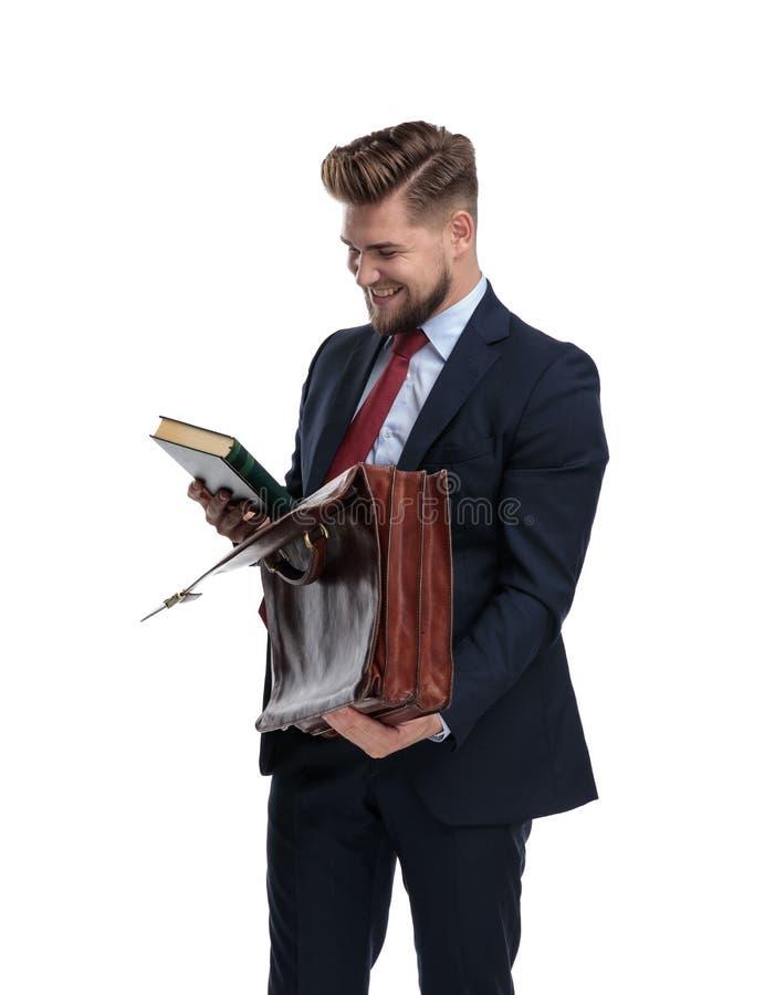 Homme d'affaires riant tout en lisant un livre et tenant sa serviette photos stock