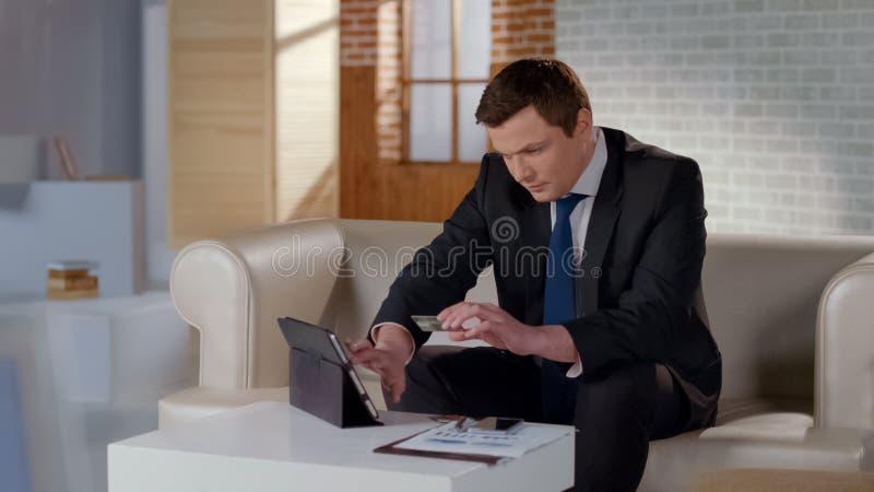 Homme d'affaires riche payant avec la carte de crédit sur le comprimé, transaction en ligne d'argent photo stock