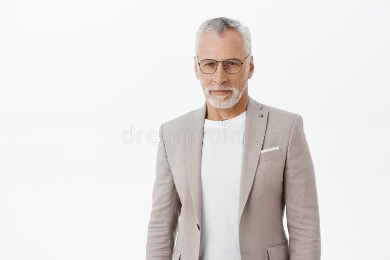 Homme d'affaires riche supérieur futé et intelligent assuré en verres un costume élégant se tenant sûr et regardant photographie stock