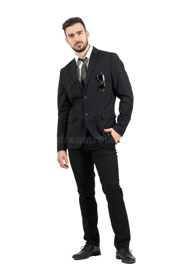 Homme d'affaires rigide strict regardant l'appareil-photo avec des lunettes de soleil dans la poche de costume photos libres de droits