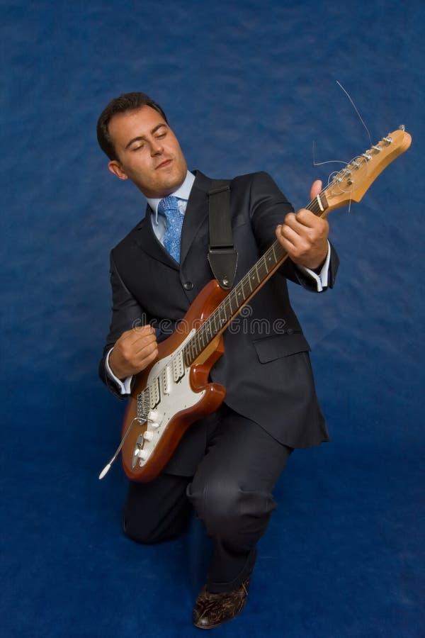 Homme d'affaires romantique avec la guitare au-dessus du bleu image libre de droits