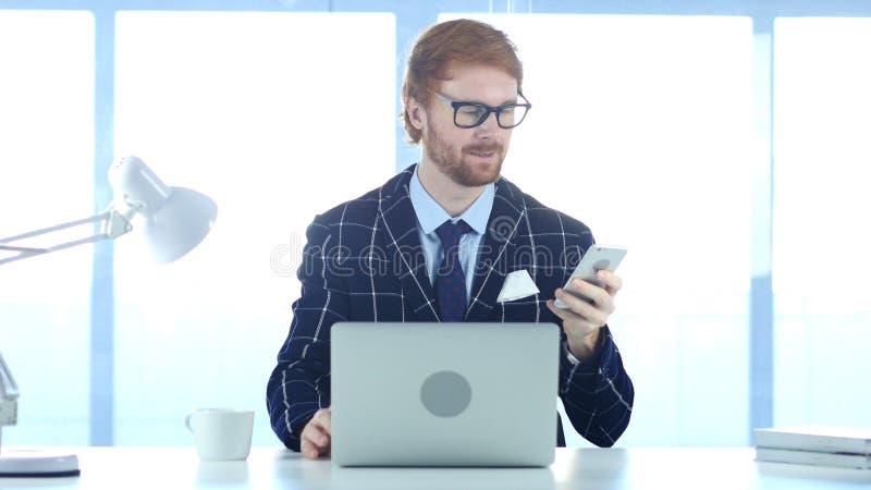 Homme d'affaires roux Using Smartphone, passant en revue en ligne au travail images stock
