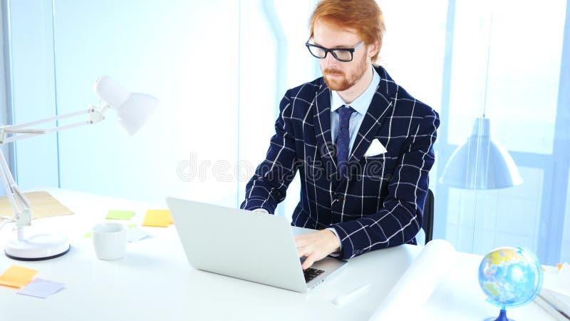 Homme d'affaires roux Working On Laptop dans le bureau, concepteur créatif d'indépendant photo libre de droits