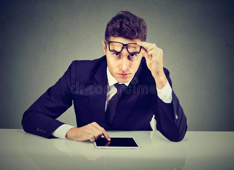 Homme d'affaires sérieux avec l'ordinateur de protection regardant l'appareil-photo images libres de droits