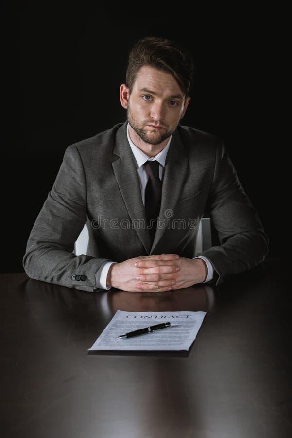 Homme d'affaires sérieux avec le cotract sur la table d'isolement sur le noir image stock