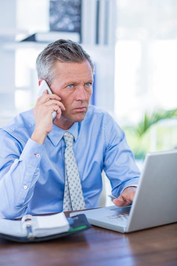 Download Homme D'affaires Sérieux Ayant L'appel Téléphonique Photo stock - Image du caucasien, laptop: 56481464