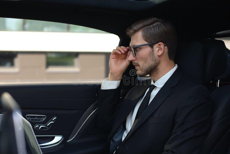 Homme d'affaires sûr réfléchi maintenant la main sur des verres tout en se reposant dans la voiture luxe image stock