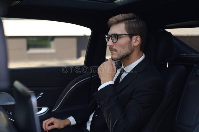 Homme d'affaires sûr réfléchi maintenant la main sur des verres tout en se reposant dans la voiture luxe photographie stock