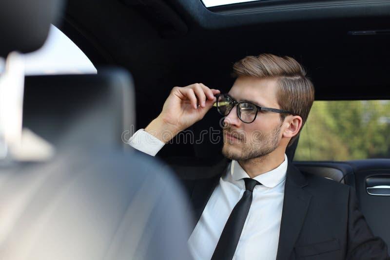 Homme d'affaires sûr réfléchi maintenant la main sur des verres tout en se reposant dans la voiture luxe photos stock